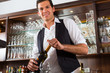 Barman standing behind bar with wine