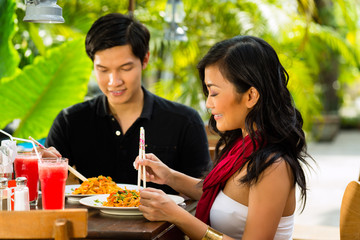 Asian man and woman in restaurant