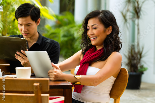 Asian people in cafe with computer