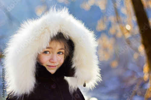 Portrait of young girl wearing fur lined coat hood