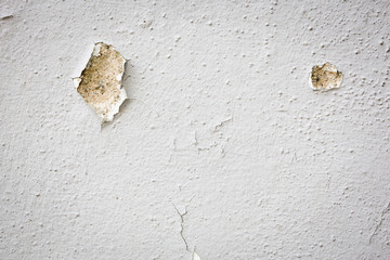 White wall with two holes and paint peeling off