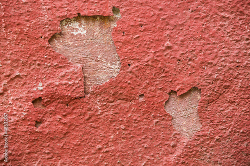 Detail of a red plaster partially peeling off