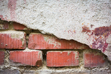Red bricks showing through white broken plaster