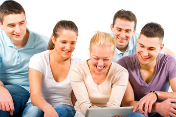 Young people sitting on a sofa, looking at a tablet
