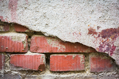 Red bricks showing through white broken plaster