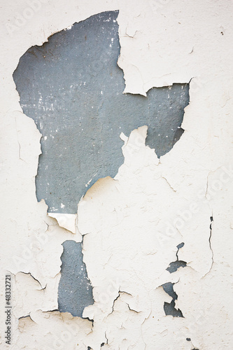 Old flaky white paint peeling off of a wall
