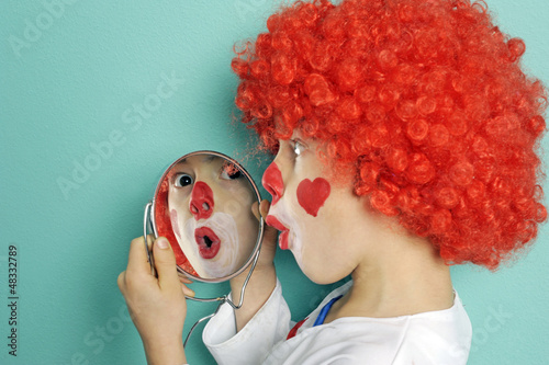 Kind verkleidet und Schminkt sich im Fasching als Clown
