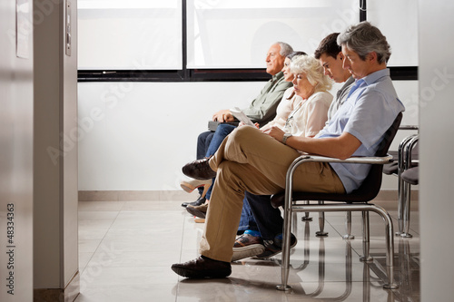 People Waiting For Doctor In Hospital Lobby