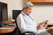 Serious Doctor Looking At Digital Tablet
