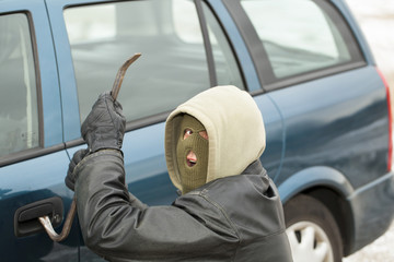 Robber with a crowbar near the car door