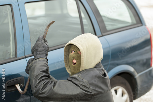 Robber with a crowbar near the car door