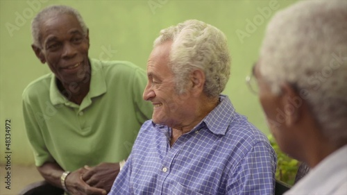 Friends, group of old men talking and laughing in park