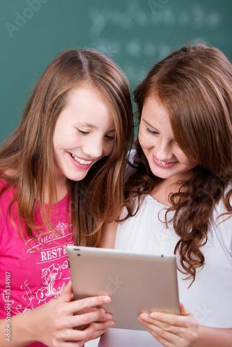 zwei schülerinnen schauen auf tablet