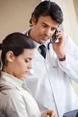 Doctor Attending Call While Standing With Colleague