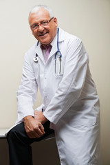 Senior Doctor Sitting On Desk