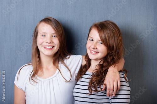 zwei freundinnen vor grauer wand
