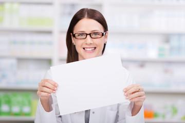 lächelnde apothekerin zeigt weißes schild