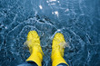 canvas print picture - rubber boots splashing in the water