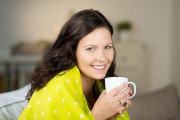 lächelnde frau wärmt sich mit tee und decke