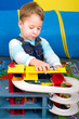 Kleiner Junge spielt mit Parkhaus
