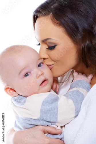 Loving mother kissing her small baby
