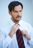 Attractive man straightening his tie