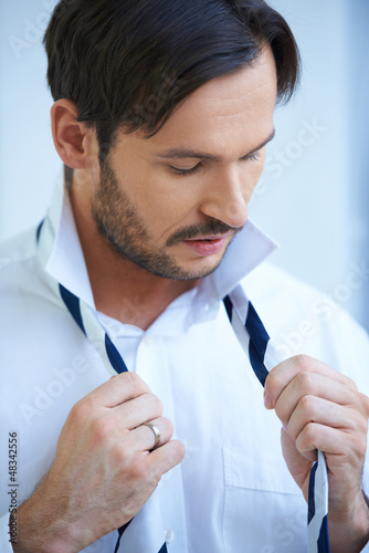 Man putting on his tie