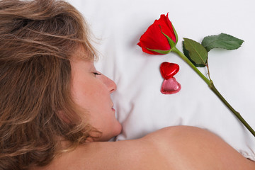 Woman asleep on Valentines Day with red rose on pillow