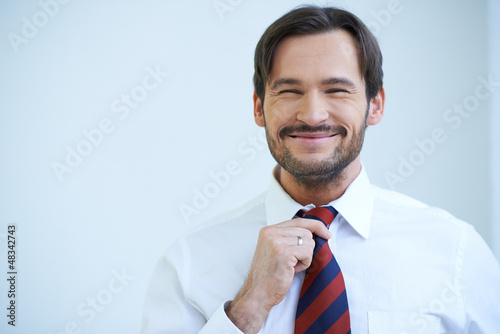 Happy bearded man straightening his tie