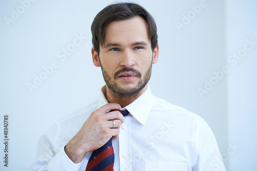 Bearded young man fiddling with his tie