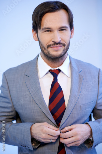 Smiling businessman buttoning his jacket
