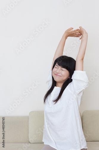 のびをする若い女性