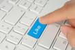 Hand pushing blue like button on keyboard close-up .