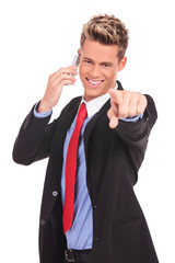 man pointing with finger while talking on the phone
