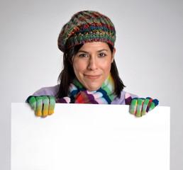 Joven mujer en otoño sujetando un panel blanco,invierno.