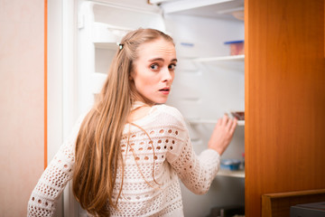 young woman looking for food in refrigerator