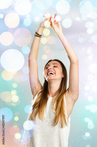 Young woman dancing with festive lights.