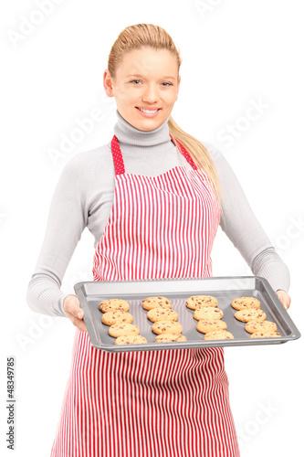 Female houswife with apron, holding freshly baked cakes