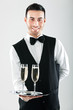 Waiter serving flutes of champagne