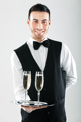 Waiter serving flutes of champagne