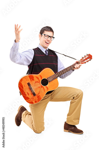 A happy male playing a guitar and singing