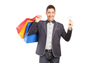 A smiling guy holding shopping bags and credit card