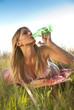junge Frau im Bikini in der Wiese liegend mit Getränk