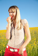 junge Frau beisst in Erdbeere in der Natur