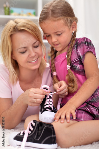 Mother teaching child how to tie shoes