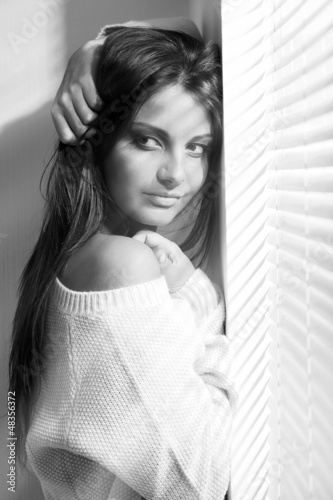 Beautiful young woman near window