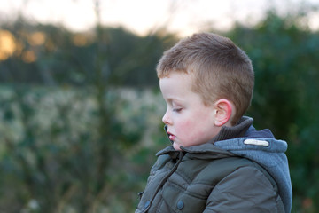 depressed young child outside in field