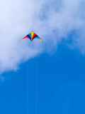A rainbow colored stunt kite against a blue sky poster