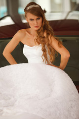 Angry bride sits on car