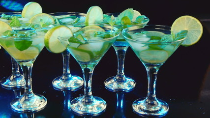Martini cocktail with lime and mint on black